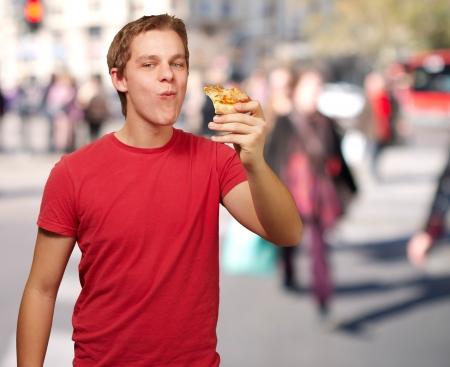negocios comida: Retrato de hombre joven que come porci�n de pizza en la calle concurrida Foto de archivo