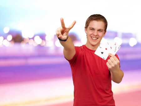 portrait of young man doing a victory gesture playing poker against a abstract background Stock Photo - 15851205