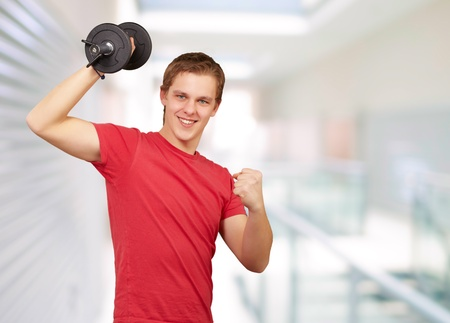 young man doing fitness with weights at entrance of building photo