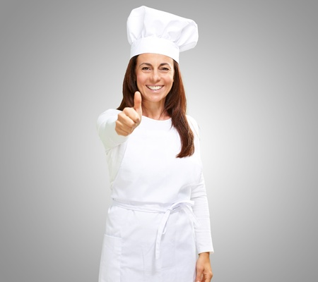 Chef woman showing thumbs up on grey background photo