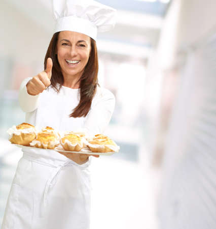 Woman chef holding baked food, outdoor photo