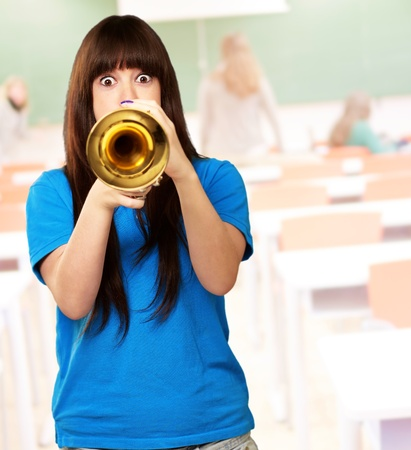 portrait of a teenager playing trumpet, indoor photo