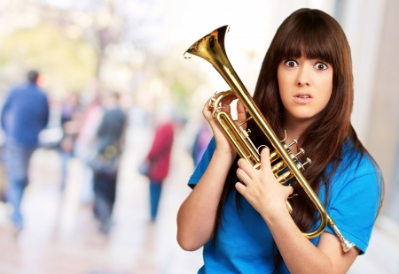 trumpeter: confused woman holding trumpet, outdoor