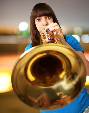 brass instrument: portrait of a young girl blowing trumpet, outdoor