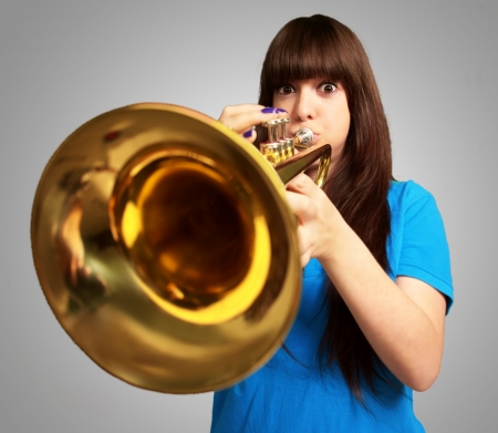 portrait of a young girl blowing trumpet on gray background