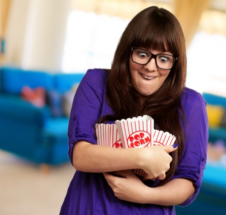 Portrait Of Young Woman Holding Popcorn Container, Indoor photo
