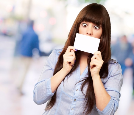 squint: Woman Holding Blank Card, Outdoor Stock Photo