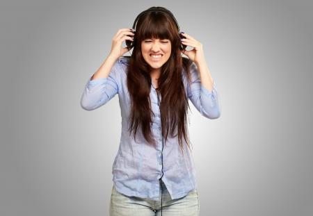irritate: Irritate Girl listening Music On Gray Background