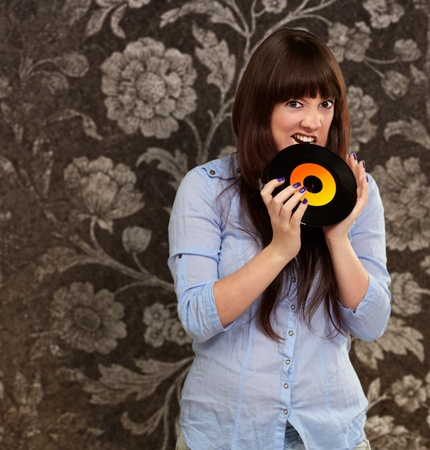 tracklist: Woman Biting Disc, Indoor Stock Photo