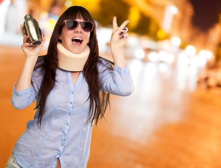 causation: Woman Wearing Neckbrace Holding A Shaker, Outdoor Stock Photo