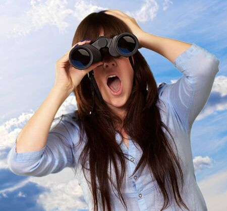 Portrait Of A Young Woman Looking Through Binoculars, Outdoor photo