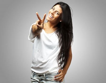 Happy Young Woman Showing Victory Sign On Grey Background photo