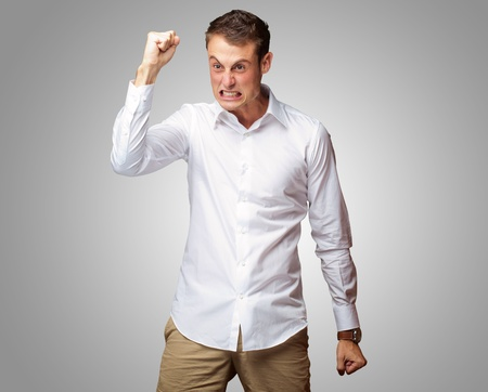 enrage: Portrait Of Angry Young Man Clenching His Fist on gray background