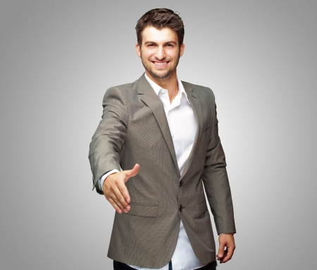 Portrait Of  Young Businessman In A Suit Holds Out His Hand For A Handshake photo
