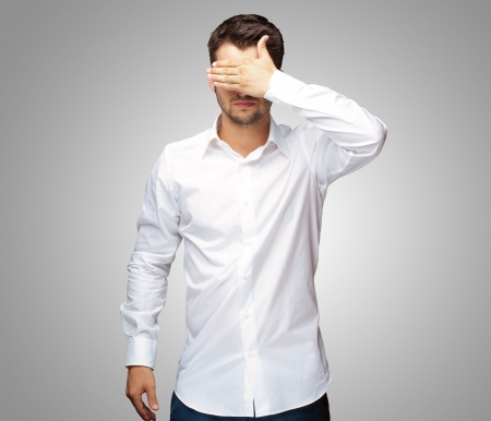 Portrait Of An Businessman Covering Eyes Isolated On Grey Background Standard-Bild