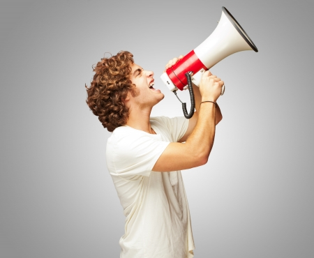 megaphone: Portrait Of Young Man Shouting With A Megaphone Isolated On Gray Background