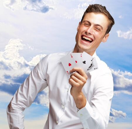 Portrait Of Young Man Showing Poker Cards, Outdoor photo