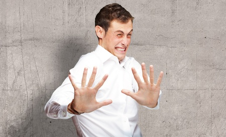 A Young Man Holding His Hands Out In Fear, Indoor Stock Photo - 16039596