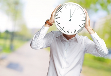 Young Man Holding Big Clock Covering His Face, Outdoor Stock Photo - 16039081