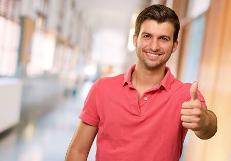 good attitude: young man smiling with thumbs up, indoor Stock Photo