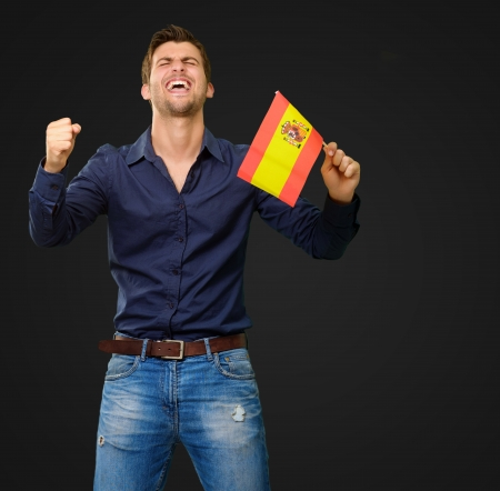 Man holding a flag and cheering on black background photo