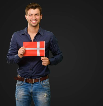 studio b: Potrait of a young man holding flag on black background