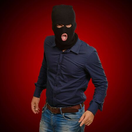 Burglar in face mask isolated on blue background photo