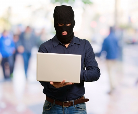 young male thief holding laptop, outdoor Stock Photo - 16039594