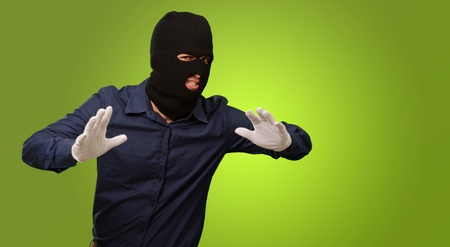 handglove: Burglar In Face Mask Isolated On Green Background Stock Photo
