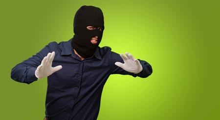 handglove: Burglar In Face Mask Isolated On Green Background Stock Photo