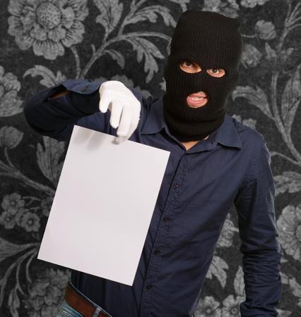 handglove: Burglar In Face Mask On Wallpaper Stock Photo