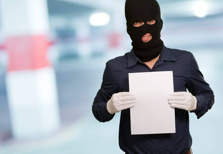 Man wearing a robber mask showing a blank paper, outdoor photo