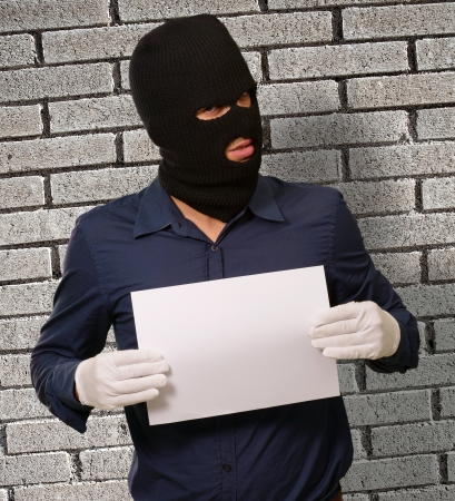 swindled: Man wearing a robber mask showing a blank paper, indoor