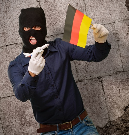 Man wearing a robber mask and holding airplane miniature and flag, indoor photo