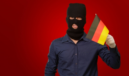 thievery: Man wearing robber mask and holding flag on red background