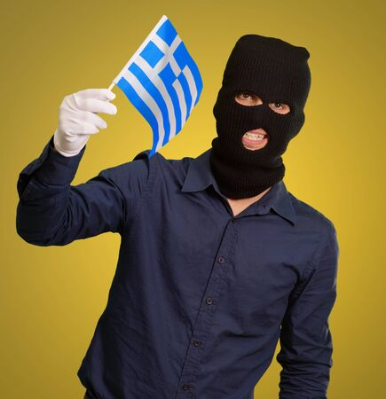 thievery: Man wearing robber mask and holding flag on yellow background Stock Photo