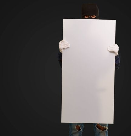 thievery: Man wearing mask holding a blank card isolated on black background