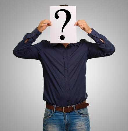 interrogative: Hombre de pie con un tablero de signo de interrogaci�n aislado en fondo gris Foto de archivo