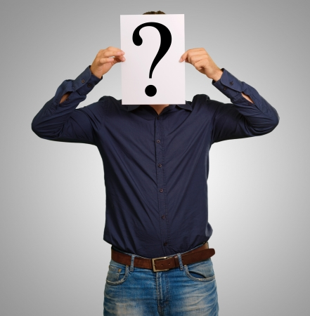 Man standing with a question mark board isolated on gray background Stock Photo