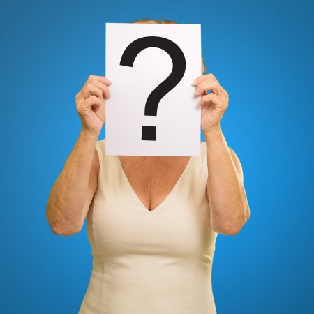 mature woman holding question mark sign isolated on blue background photo