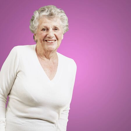 pretty senior woman smiling against a pink background