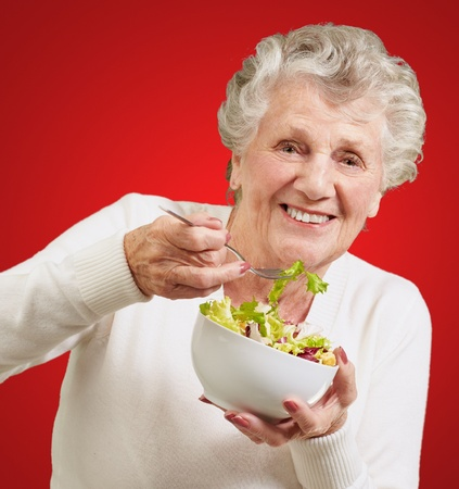 over eating: portrait of senior woman eating a fresh salad over red background