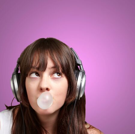 portrait of young woman listening to music with bubble gum over purple photo