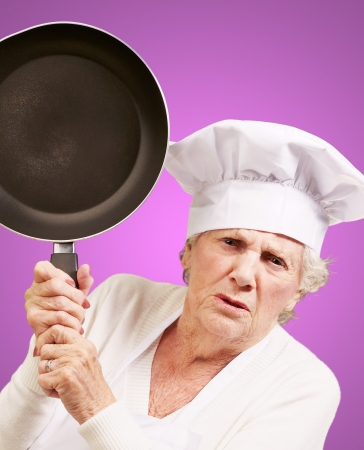Cook senior woman angry trying to hit with pan over purple background photo