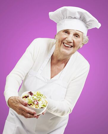 senior woman cook holding a bowl with salad against a pink background photo