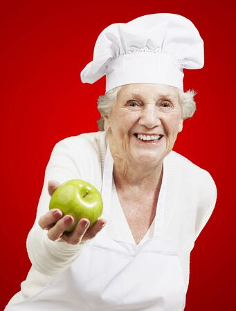 senior woman cook offering a green apple against a red background photo