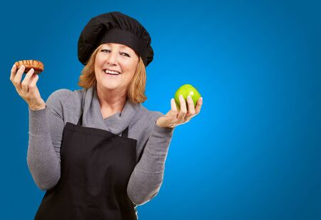 Portrait Of A Woman Holding Fruit On Blue Background photo