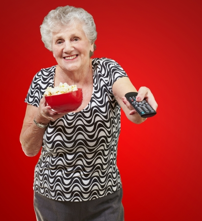 programm: portrait of happy senior woman looking the tv over red background