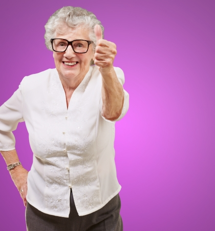 portrait of adorable senior woman doing good gesture over purple photo
