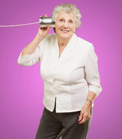 portrait of senior woman hearing with metal tin can over pink background Stock Photo - 16039299